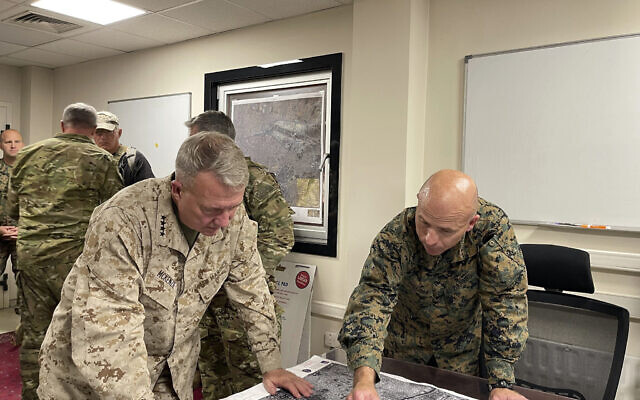 US Marine Corps Gen. Frank McKenzie, center left, the commander of U.S. Central Command, and U.S. Marine Brig. Gen. Farrell J. Sullivan, the commander of the Naval Amphibious Task Force 51/5th Marine Expeditionary Brigade, review an aerial photo, at Hamid Karzai International Airport, Kabul, Afghanistan, Tuesday, Aug. 17, 2021. (Capt. William Urban/U.S. Navy via AP)