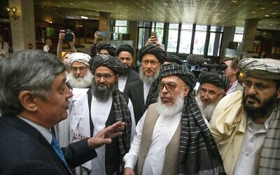 In this Tuesday, May 28, 2019 file photo, Russian presidential envoy to Afghanistan Zamir Kabulov, left, speaks to Mullah Abdul Ghani Baradar, the Taliban group's top political leader, third left, Sher Mohammad Abbas Stanikzai, the Taliban's chief negotiator, third right, and other members of the Taliban delegation prior to their talks in Moscow, Russia.  (AP Photo/Alexander Zemlianichenko, File)
