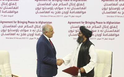 In this Feb. 29, 2020 file photo, US peace envoy Zalmay Khalilzad, left, and Mullah Abdul Ghani Baradar, the Taliban group's top political leader, shake hands after signing a peace agreement between Taliban and US officials in Doha, Qatar. (AP Photo/Hussein Sayed, File)