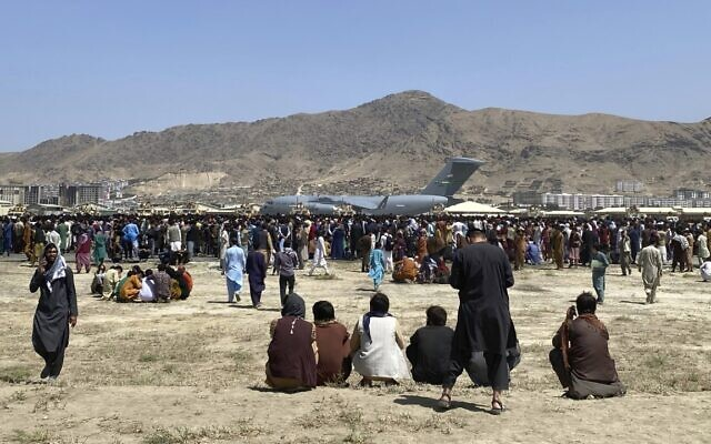 Hundreds of people gather near a US Air Force C-17 transport plane at the perimeter of the international airport in Kabul, Afghanistan, on Monday, August 16, 2021. (AP Photo/Shekib Rahmani)