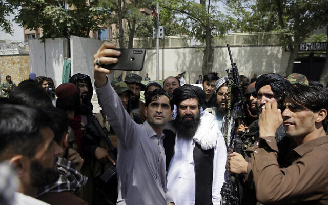An Afghan takes a selfie with Taliban fighters on patrol in Kabul, Afghanistan, on August 19, 2021. (AP/Rahmat Gul)