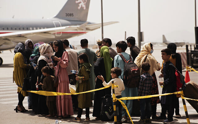 In this photo provided by the US Marine Corps, civilians prepare to board a plane during an evacuation at Hamid Karzai International Airport, Kabul, Afghanistan, on August 18, 2021. (Staff Sgt. Victor Mancilla/US Marine Corps via AP)
