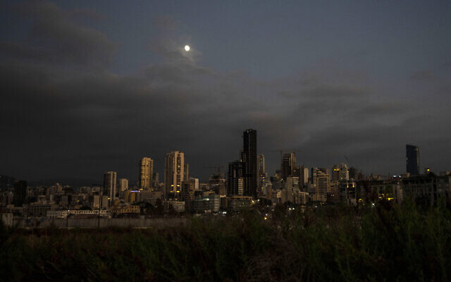 The moon rises over the capital city of Beirut as it remains in darkness during a power outage, Lebanon, Thursday, Aug. 19, 2021.(AP/ Hassan Ammar)