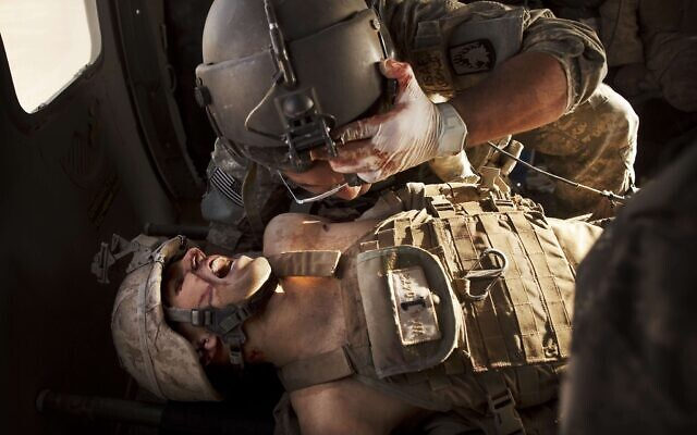 """US Army flight medic SGT Jaime Adame, top, cares for seriously wounded Marine CPL Andrew Smith following an insurgent attack on board a medevac helicopter, May 15, 2011, from the US Army's Task Force Lift """"Dust Off"""", Charlie Company 1-214 Aviation Regiment north of Sangin, in the volatile Helmand Province of southern Afghanistan. (AP Photo/Kevin Frayer)"""