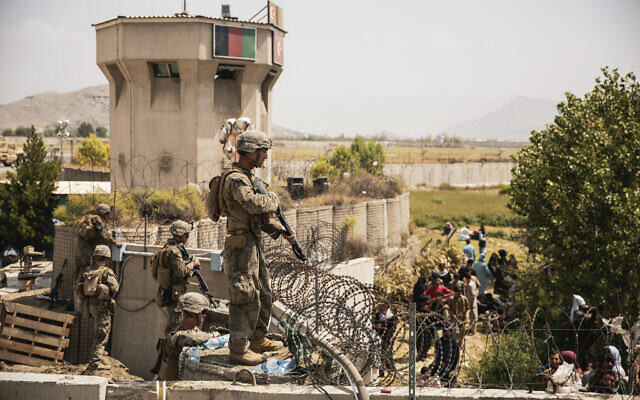 In this image provided by the US Marine Corps, Marines assist with security at an evacuation control checkpoint during an evacuation at Hamid Karzai International Airport in Kabul, Afghanistan, on August 20, 2021. (Staff Sgt. Victor Mancilla/US Marine Corps via AP)