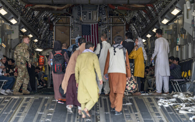 In this image provided by the US Air Force, a US Air Force loadmaster, assigned to the 816th Expeditionary Airlift Squadron, assists evacuees aboard a C-17 Globemaster III aircraft in support of Operation Allies Refuge at Hamid Karzai International Airport in Kabul, Afghanistan, August 20, 2021. (Senior Airman Taylor Crul/US Air Force via AP)