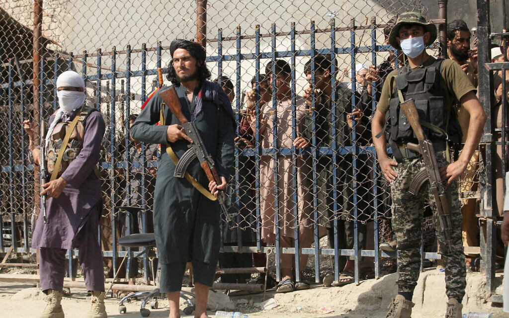 A Pakistani paramilitary soldier, right, and Taliban fighters stand guard on their respective sides  at a border crossing point between Pakistan and Afghanistan, in Torkham, in Khyber district, Pakistan, August 21, 2021. (AP Photo/Muhammad Sajjad)