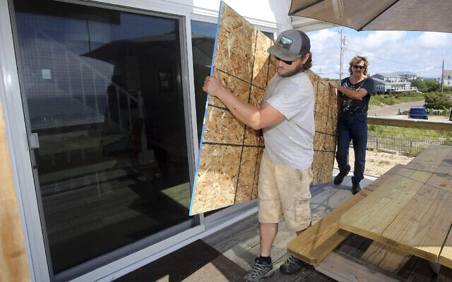 James Masog, center, and Gary Tavares, right, move particle board into place to board up the sliding glass doors of a clients house in Charlestown, R.I., ahead of Hurricane Henri, August 21, 2021. (AP Photo/Stew Milne)