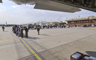 Afghans stand in line to be evacuated onto an Italian Airforce C130J plane from Kabul airport, Sunday, Aug. 22, 2021. (Italian Defense Ministry via AP)