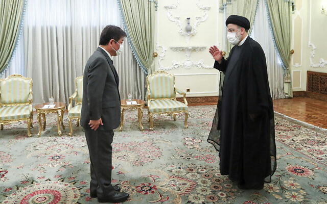 Iranian President Ebrahim Raisi, right, welcomes Japanese Foreign Minister Toshimitsu Motegi for their meeting at the presidency office, in Tehran, Iran, on August 22, 2021. (Iranian Presidency Office via AP)