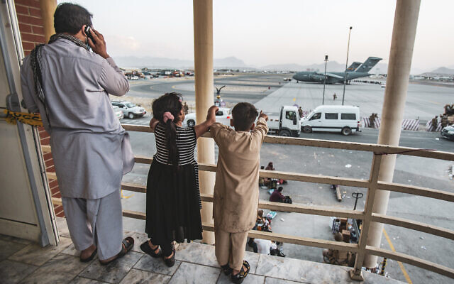 In this image provided by the US Marine Corps, two children point at an aircraft after they have been manifested to depart, at Hamid Karzai International Airport, Kabul, Afghanistan, August 21, 2021. (1st Lt. Mark Andries/U.S. Marine Corps via AP)