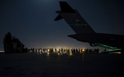 In this image provided by the US Air Force, US Air Force aircrew, assigned to the 816th Expeditionary Airlift Squadron, prepare to load qualified evacuees aboard a US Air Force C-17 Globemaster III aircraft in support of the Afghanistan evacuation at Hamid Karzai International Airport, Kabul, Afghanistan, August 21, 2021. (Senior Airman Taylor Crul/U.S. Air Force via AP)