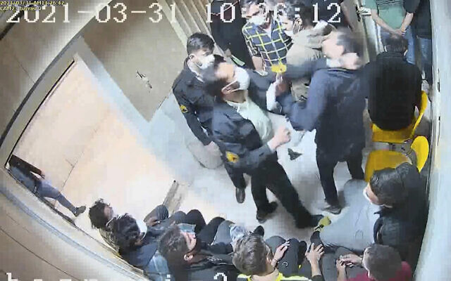 """In this undated frame grab taken from video shared with The Associated Press by a self-identified hacker group called """"The Justice of Ali,"""" a guard beats a prisoner, at Evin prison in Tehran, Iran. (The Justice of Ali via AP)"""
