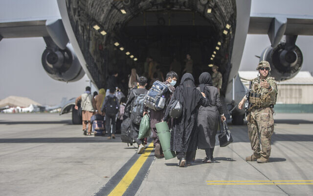 In this image provided by the US Marine Corps, families begin to board a US Air Force Boeing C-17 Globemaster III during an evacuation at Hamid Karzai International Airport in Kabul, Afghanistan, on August 23, 2021. (Sgt. Samuel Ruiz/US Marine Corps via AP)