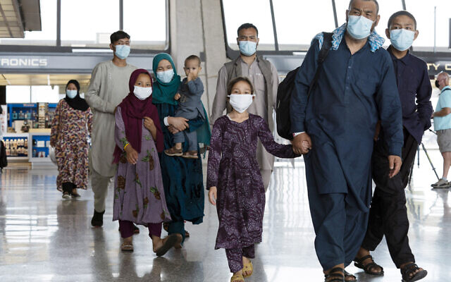 Families evacuated from Kabul, Afghanistan, walk through the terminal before boarding a bus after they arrived at Washington Dulles International Airport, in Chantilly, Va., on Monday, Aug. 23, 2021. (AP Photo/Jose Luis Magana)