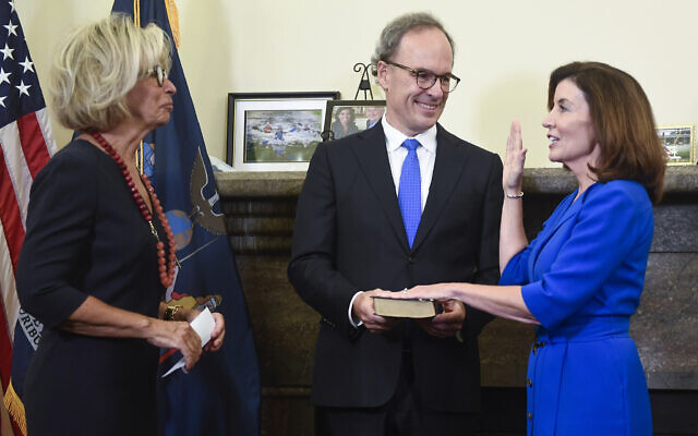 New York Chief Judge Janet DiFiore, left, swears in Kathy Hochul, right, as the first woman to be New York's governor while her husband, Bill Hochul, holds a bible during a swearing-in ceremony in the Red Room at the state Capitol, early Tuesday, Aug. 24, 2021, in Albany, N.Y. (AP Photo/Hans Pennink, Pool)