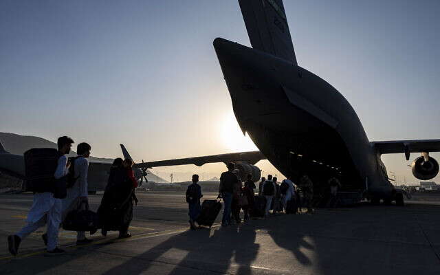In this image provided by the U.S. Air Force, US Air Force airmen guide evacuees aboard a US Air Force C-17 Globemaster III at Hamid Karzai International Airport in Kabul, Afghanistan, Tuesday, Aug. 24, 2021. (Senior Airman Taylor Crul/U.S. Air Force via AP)