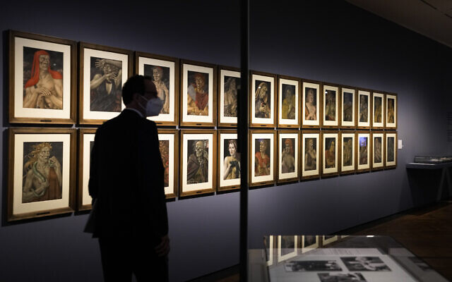 A women takes a photo of the artwork 'Demons of the Hour' by artist Werner Peiner at the exhibition 'Divinely Gifted List' at the German Historic Museum in Berlin, Germany, on August 25, 2021. (AP Photo/Markus Schreiber)