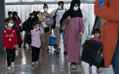 Families evacuated from Kabul, Afghanistan, walk through the terminal before boarding a bus after they arrived at Washington Dulles International Airport, in Chantilly, Va., on Wednesday, Aug. 25, 2021. (AP Photo/Jose Luis Magana)