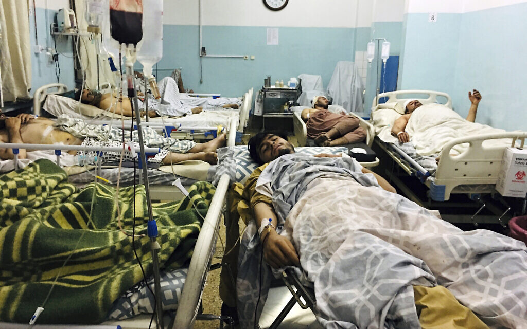Wounded Afghans lie on a bed at a hospital after a deadly explosion outside the airport in Kabul, Afghanistan, Thursday, Aug. 26, 2021.  (AP/Mohammad Asif Khan)