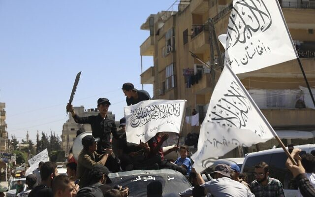 Members of the Hay'at Tahrir al-Sham, a Sunni Islamist militant group, wave the Taliban flags as they celebrate the Taliban takeover of Afghanistan, in the city of Idlib, Friday, Aug. 20, 2021 (AP Photo/Ghaith Alsayed)
