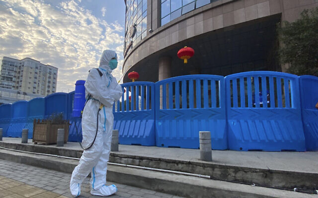 In this Feb. 6, 2021 photo, a worker in protective overalls carries disinfecting equipment while walking outside the Wuhan Central Hospital, where Li Wenliang, the whistleblower doctor who sounded the alarm and was reprimanded by local police for it in the early days of Wuhan's pandemic, worked in Wuhan in central China. (AP/Ng Han Guan)