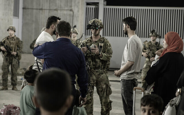 In this image provided by the US Marine Corps, soldiers with the 82nd Airborne Division assist evacuees during an evacuation at Hamid Karzai International Airport, Kabul, Afghanistan, August 25, 2021. (Staff Sgt. Victor Mancilla/U.S. Marine Corps via AP)