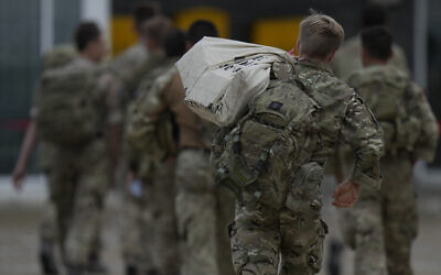 Members of the British armed forces 16 Air Assault Brigade walk to the air terminal after disembarking a RAF Voyager aircraft at Brize Norton, England, as they return from helping in operations to evacuate people from Kabul airport in Afghanistan, on August 28, 2021. (AP Photo/Alastair Grant, Pool)