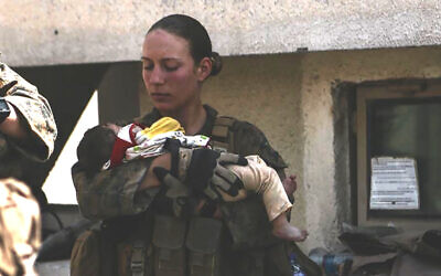 This undated photo provided by the US Department of Defense twitter page posted August 20, 2021 shows Sgt. Nicole Gee holding a baby at Hamid Karzai International Airport in Kabul, Afghanistan. (US Department of Defense via AP)