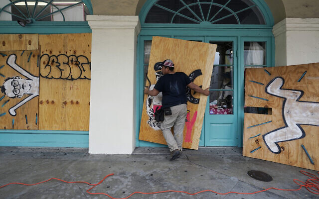 In preparation of Hurricane Ida, a US worker attaches protective plywood to windows and doors of a business in the French Quarter in New Orleans, August 28, 2021. (AP Photo/Eric Gay)