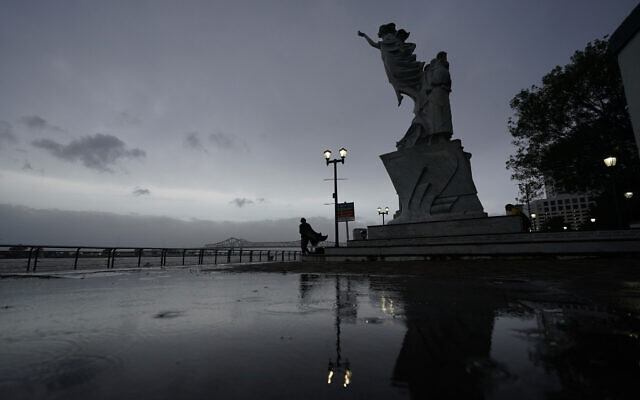 A man walks along the Mississippi River near the French Quarter as the sun rises and the early effects of Hurricane Ida are felt, Sunday, Aug. 29, 2021, in New Orleans, La. (AP Photo/Eric Gay)