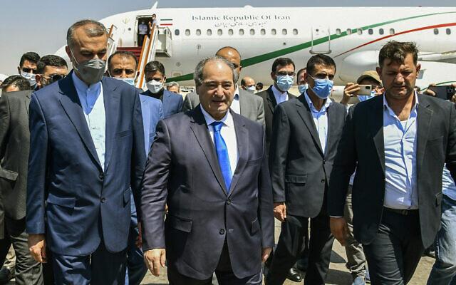 Syria's Foreign Minister Faisal Mekdad, center left, receives Iran's new Foreign Minister Hossein Amir-Abdollahian, left, in Damascus, Syria, August 29, 2021. (SANA via AP)