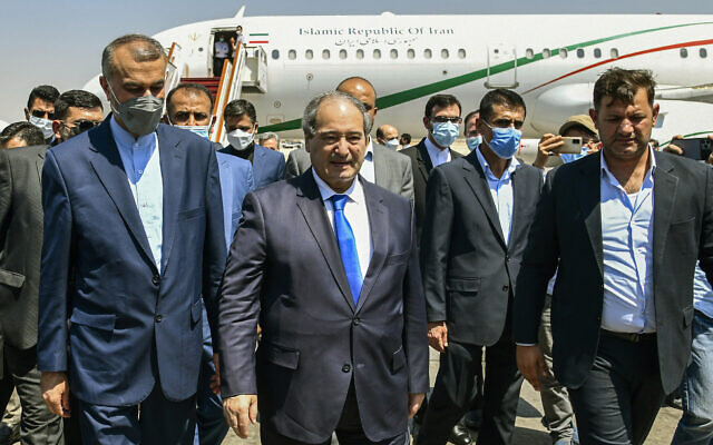 In this photo released by the Syrian official news agency SANA, Syria's Foreign Minister Faisal Mekdad, center left, receives Iran's new Foreign Minister Hossein Amir-Abdollahian, left, in Damascus, Syria, August 29, 2021. (SANA via AP)