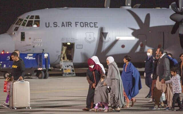 Families evacuated from Kabul, Afghanistan, walks past an US air force airplane that flew them at Kosovo's capital Pristina International Airport on August 29, 2021. (AP Photo/Visar Kryeziu)