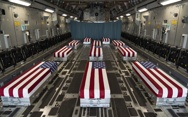 In this image provided by the US Air Force, flag-draped transfer cases line the inside of a transport plane Sunday, Aug. 29, 2021, prior to a dignified transfer at Dover Air Force Base, Del. The fallen service members were killed while supporting non-combat operations in Kabul, Afghanistan. (Jason Minto/US Air Force via AP)