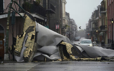 A section of roof that was blown off of a building in the French Quarter by Hurricane Ida winds blocks an intersection, Sunday, August 29, 2021, in New Orleans. (AP Photo/Eric Gay)