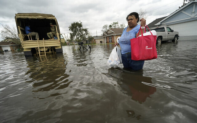 Jerilyn Collins returns to her destroyed home with the assistance of a Louisiana National Guard high-water vehicle to retrieve medicine for herself and her father, and a few possessions, after she evacuated from rising floodwater in the aftermath of Hurricane Ida in LaPlace, Louisiana, August 30, 2021. (AP Photo/Gerald Herbert)