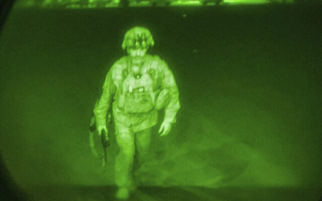 In this image made through a night vision scope, Maj. Gen. Chris Donahue, commander of the US Army 82nd Airborne Division, XVIII Airborne Corps, boards a C-17 cargo plane at Hamid Karzai International Airport in Kabul, Afghanistan, August 30, 2021, as the final American service member to depart Afghanistan. (US Central Command via AP)