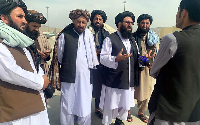 Taliban officials are interviewed by journalists inside the Hamid Karzai International Airport after the US withdrawal in Kabul, Afghanistan, Tuesday, Aug. 31, 2021. (AP Photo/Kathy Gannon)