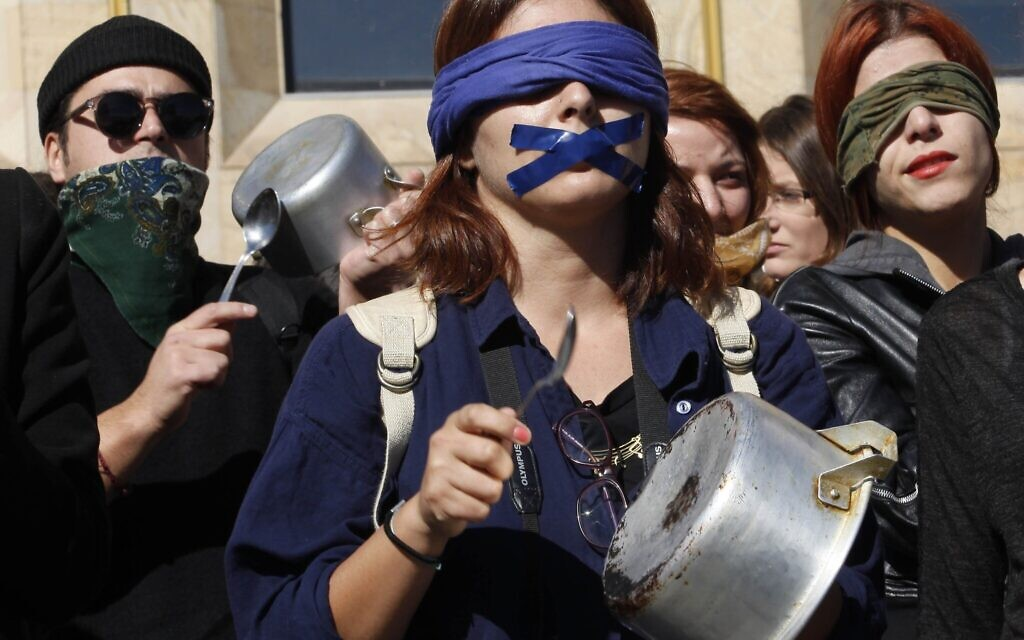 Illustrative: Demonstrators bang pots and pans at a protest rally against domestic violence in Tbilisi, Georgia, Tuesday, Oct. 21, 2014. (AP Photo/Shakh Aivazov)