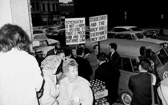 Protesters hold placards outside the courthouse where Jack Ruby's trial and sentencing was held in Dallas, Texas, March 9, 1964.  (AP Photo)