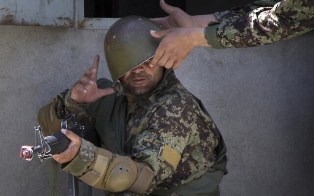 A military instructor adjusts the helmet of an Afghan Army soldier during a house-to-house search at a training facility in the outskirts of Kabul, Afghanistan, May 8, 2013. (Anja Niedringhaus/AP)
