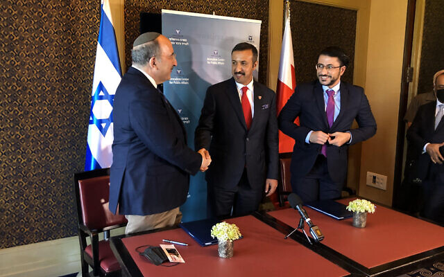 Bahrain's Undersecretary for International Relations Sheikh Abdullah bin Ahmad al Khalifa (c) shakes hands with JCPA President Dore Gold (l) at the King David Hotel in Jerusalem, August 8, 2021 (Lazar Berman/Times of Israel)
