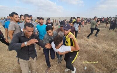 Palestinians carry a demonstrator wounded during clashes with Israeli soldiers along the Gaza border, on Saturday, August 21, 2021. (Credit: Hassan Islayeh)
