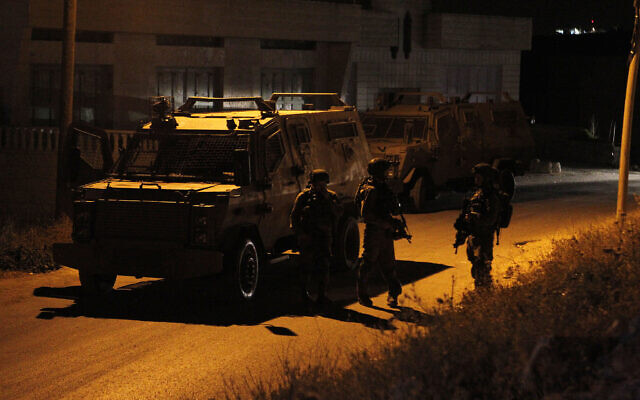 Illustrative: IDF soldiers stand guard during a search in the West Bank village of Yatta, June 15, 2016. (Wisam Hashlamoun/Flash90)