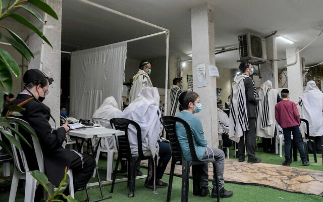 Illustrative: Jews pray outside in the city of Bnei Brak on January 14, 2021, during the 3rd lockdown due to the COVID-19 coronavirus pandemic. (Yossi Zeliger/Flash90)