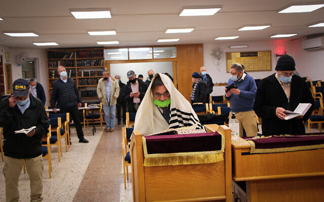 Jewish men wear protective face masks as they pray at a synagogue in the settlement of Efrat, in the Etzion Bloc, March 3, 2021. (Gershon Elinson/Flash90)