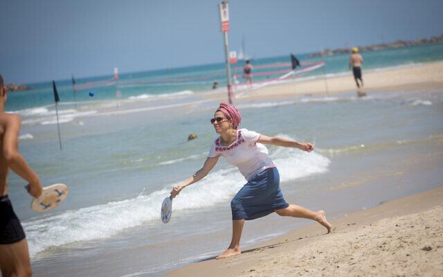 Israelis enjoy the beach in Tel Aviv on a hot summer day. June 29, 2021. (Miriam Alster/FLASH90)