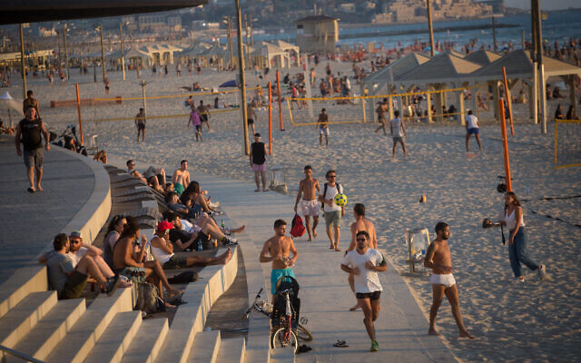Illustrative: Israelis at the beach in Tel Aviv, on a hot summer day, July 6, 2021. (Miriam Alster/Flash90)