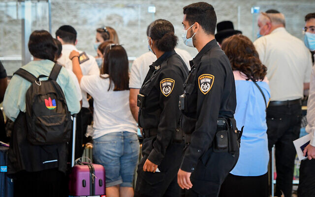 Illustrative -- Police officers enforce COVID-19 regulations at Ben Gurion International Airport, on July 19, 2021. (Avshalom Sassoni/Flash90)
